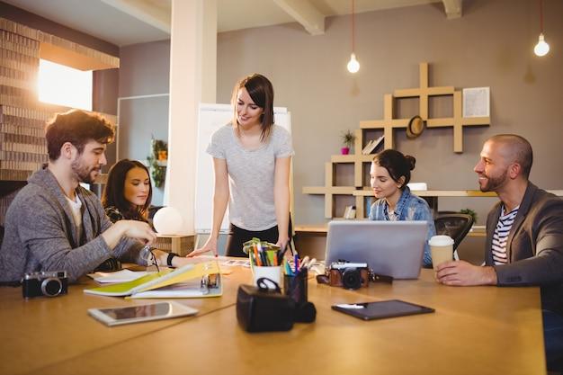 Vrouwelijke grafisch ontwerper discussie met collega's