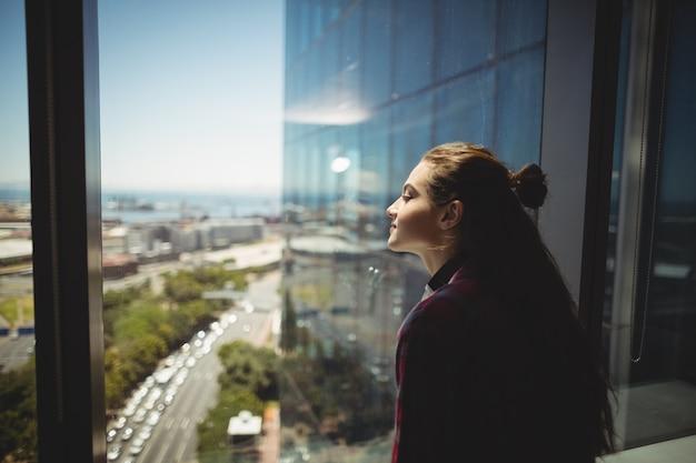 Vrouwelijke grafisch ontwerper kijkt door raam