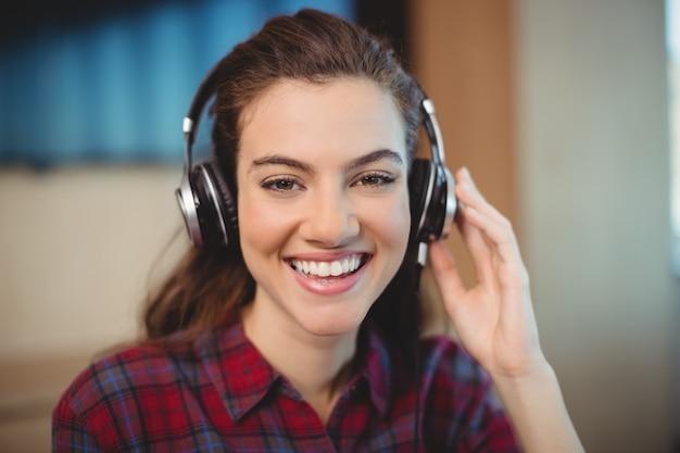 Vrouwelijke grafisch ontwerper luisteren muziek op koptelefoon