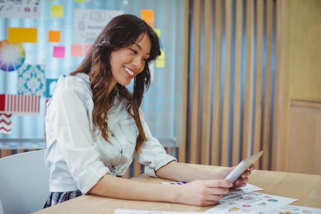 Vrouwelijke grafisch ontwerper met behulp van digitale tablet aan balie