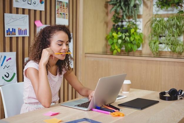 Vrouwelijke grafisch ontwerper met behulp van laptop