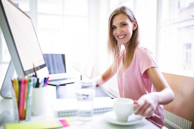 Vrouwelijke grafisch ontwerper met koffie aan balie