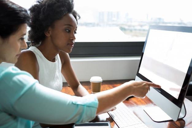 Vrouwelijke grafisch ontwerper wijst naar desktop-pc