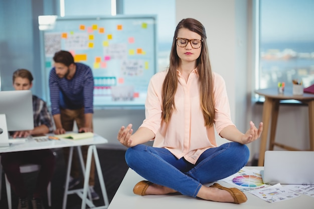 Vrouwelijke grafisch ontwerper zittend op tafel en mediteren