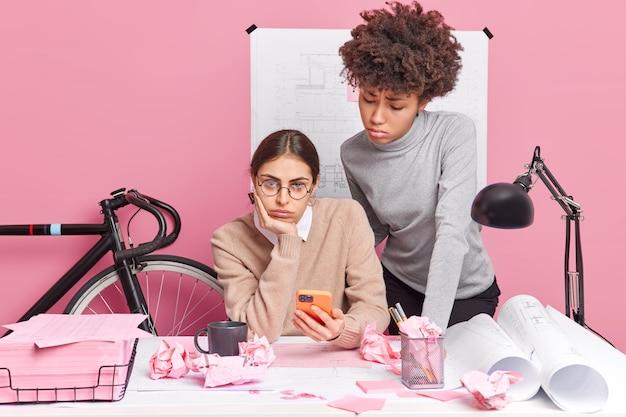 Vrouwelijke grafisch ontwerpers die ongelukkig zijn met falen tijdens het werken, poseren in een coworking-ruimte en gebruiken een moderne smartphone