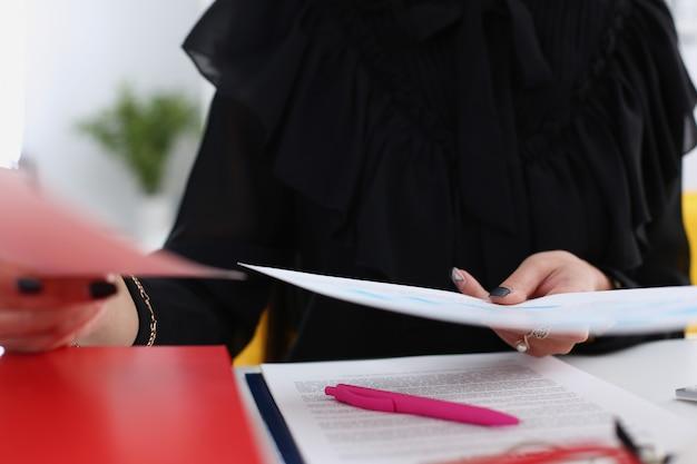Vrouwelijke greep in arm papieren zitten aan tafel