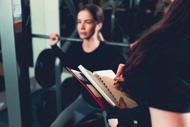 Vrouwelijke gymnastiektrainer die op agenda schrijven
