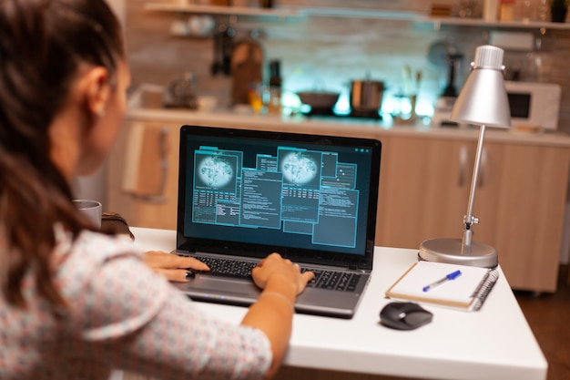 Vrouwelijke hacer die 's avonds laat vanuit huis de beveiligingsfirewall kraakt. programmeur die een gevaarlijke malware schrijft voor cyberaanvallen met behulp van een prestatielaptop tijdens middernacht.