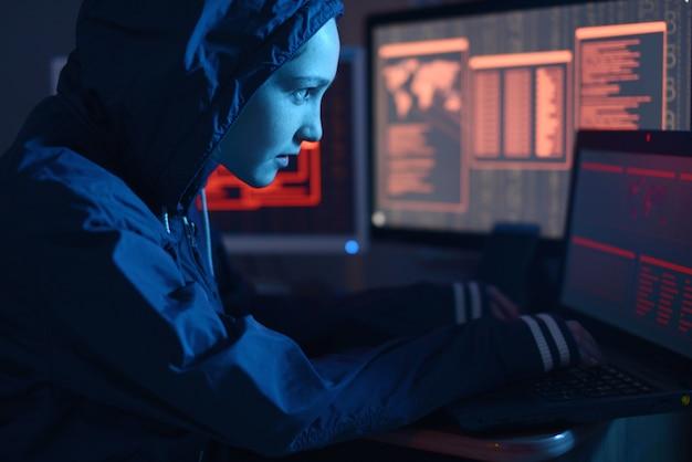 Vrouwelijke hacker in een hoodie die een database aanvalt