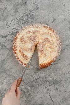 Vrouwelijke hand appeltaart snijden met mes op marmeren oppervlak.