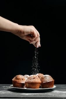 Vrouwelijke hand bestrooit vers gebakken muffins met poedersuiker.