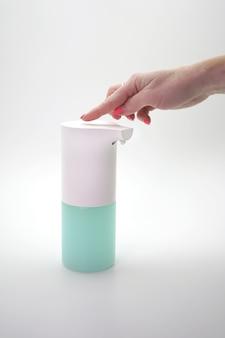 Vrouwelijke hand bevat automatische dispenser, ontsmettingsmiddel op een geïsoleerde muur. handdesinfectie, preventie van de coronavirus pandemie