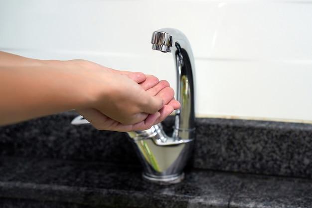 Vrouwelijke hand controleert het water in de kraan