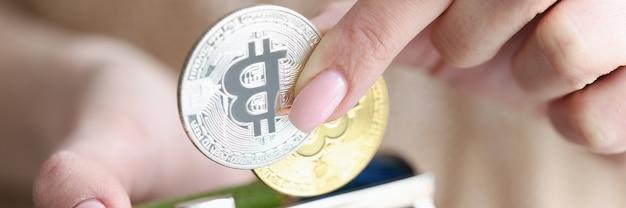 Vrouwelijke hand die bitcoins in portefeuilleclose-up zet