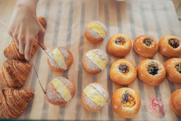 Vrouwelijke hand die cake uit de vitrine in de bakkerij haalt