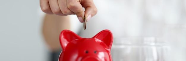 Vrouwelijke hand die contant geldmunten werpt in rood spaarvarken close-up thuisboekhouding concept