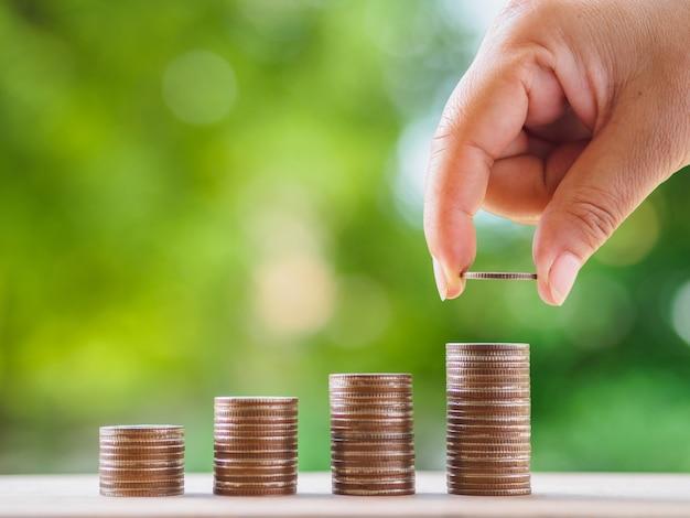 Vrouwelijke hand die de stapel groeiende zaken van het geldmuntstuk zetten