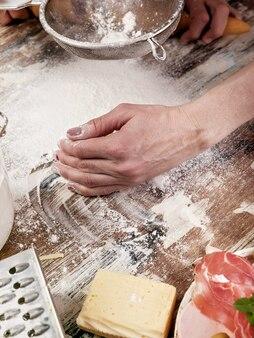 Vrouwelijke hand die deeg op een houten lijst maakt. detailopname. verticaal schot