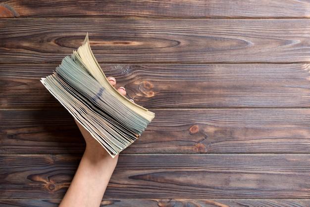 Vrouwelijke hand die dikke bundel van diverse dollarbankbiljetten houdt