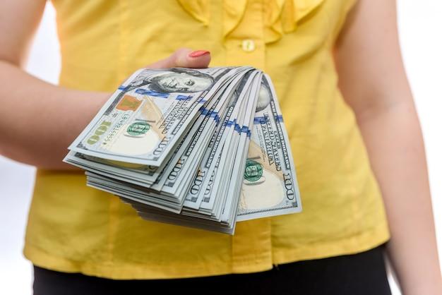 Vrouwelijke hand die dollarbankbiljetten in ventilator aanbiedt