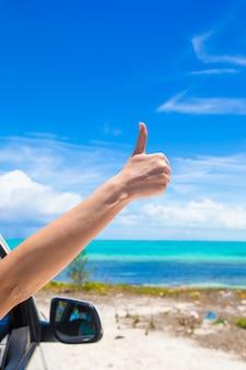 Vrouwelijke hand die duimen op het strand toont
