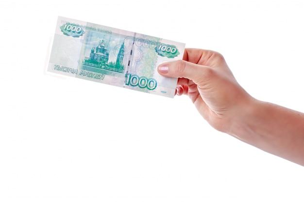 Vrouwelijke hand die een bankbiljet van duizend roebels houdt