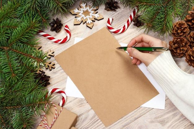 Vrouwelijke hand die een brief van kerstmis schrijft