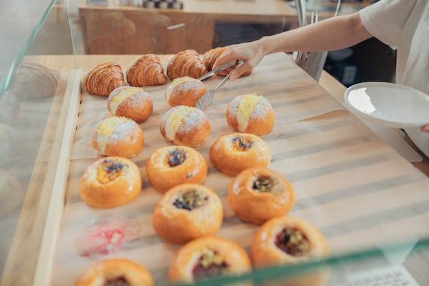 Vrouwelijke hand die een broodje uit de vitrine in de bakkerij haalt