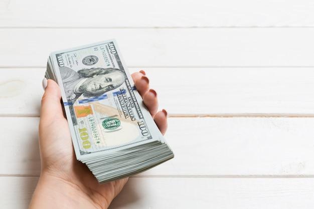 Vrouwelijke hand die een bundel van geld houdt