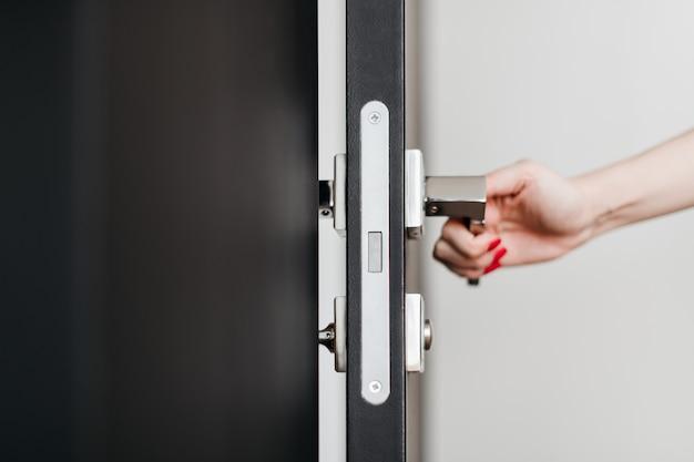 Vrouwelijke hand die een deur opent met behulp van de knop in het appartement