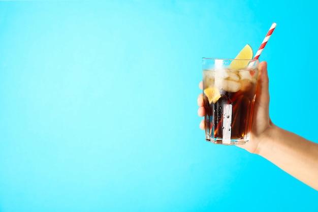 Vrouwelijke hand die een glas met ijskola, buisje en kalkplak houdt