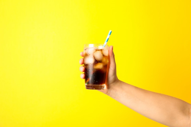 Vrouwelijke hand die een glas met ijskola en buisje houdt