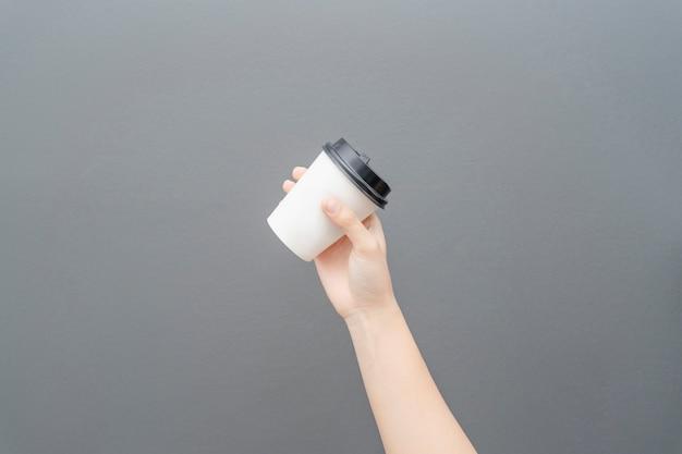 Vrouwelijke hand die een koffiedocument kop op grijs houdt