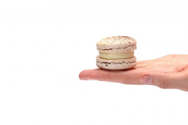 Vrouwelijke hand die een makaron houdt