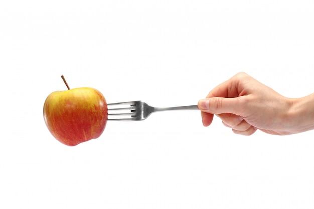 Vrouwelijke hand die een metaalvork met een verse appel houdt