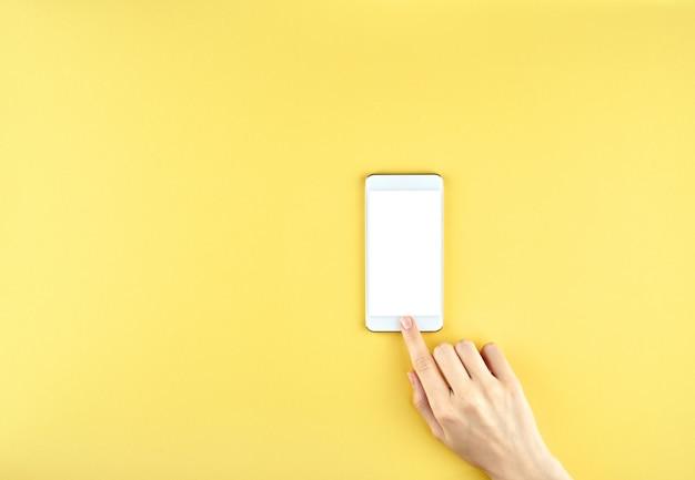 Vrouwelijke hand die een modern gadget houdt en met vinger op geel richt