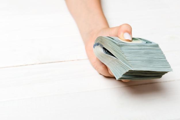 Vrouwelijke hand die een pak geld houdt