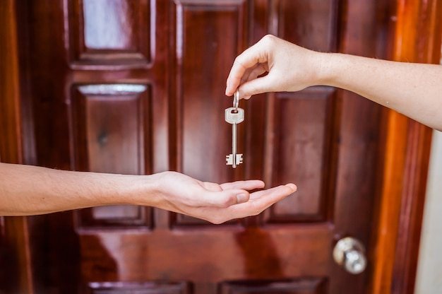 Vrouwelijke hand die een sleutel geeft aan het huis man op achtergrond van houten deur. het bezit van onroerend goed concept