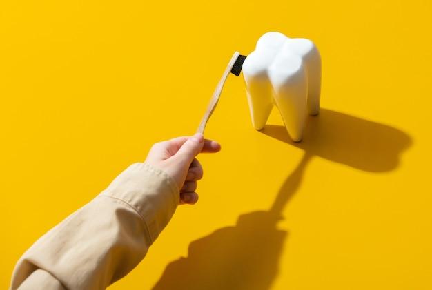 Vrouwelijke hand die een tand op gele oppervlakte borstelt
