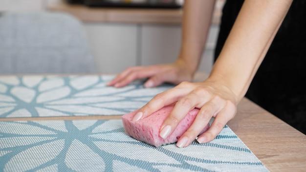 Vrouwelijke hand die een vuile tafel met een spons binnenshuis wast
