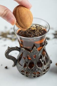 Vrouwelijke hand die een zoet okkernootvormig koekje in een kopje thee dompelt.