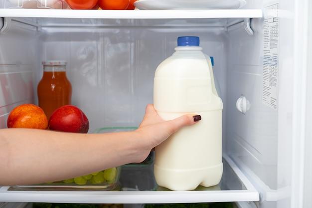 Vrouwelijke hand die fles melk uit een koelkast neemt