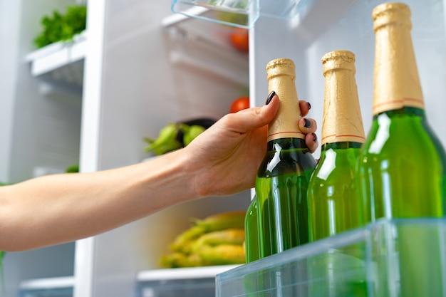 Vrouwelijke hand die flesje bier uit een koelkast neemt