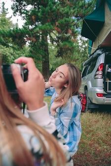 Vrouwelijke hand die foto neemt naar mooie gelukkige jonge vrouw op de camping met haar 4x4-voertuig met tent op het dak op de achtergrond
