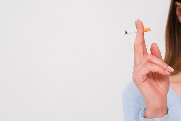 Vrouwelijke hand die gebroken sigaret houdt die op witte achtergrond wordt geïsoleerd
