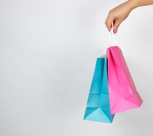 Vrouwelijke hand die gekleurde document het winkelen verpakkende zakken houdt
