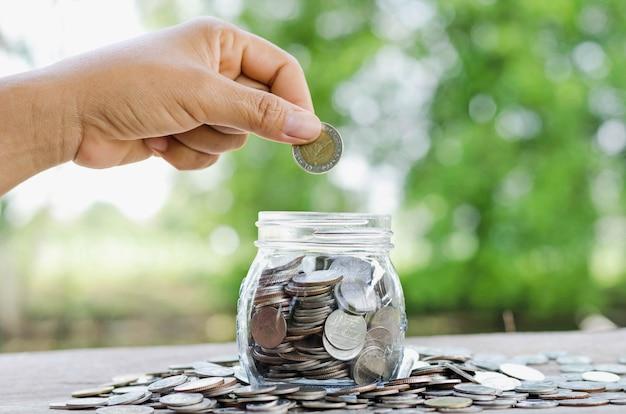 Vrouwelijke hand die geldmuntstukken in kruikconcept en groene aardachtergrond zetten