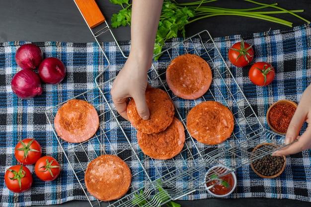 Vrouwelijke hand die geroosterde salamiplakken van rooster neemt.