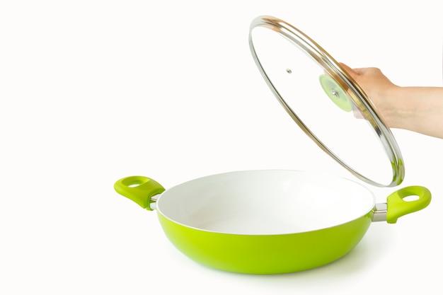 Vrouwelijke hand die het deksel van de pan houdt. geïsoleerd