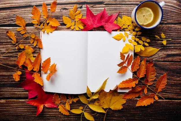 Vrouwelijke hand die in een kogeldagboek schrijft. de lege blocnotepagina met vrouwen omcirkelt glazen bovenop in een comfortabele ruimte met de herfst oranje, gele en rode bladeren op een houten lijst.